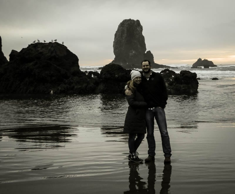 A couple at cannon beach at sunset