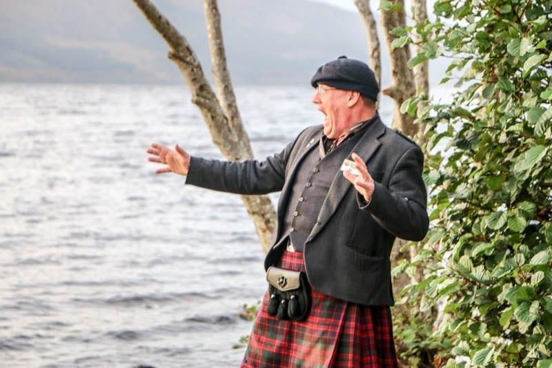A Scottish Highlander pretending to see the Loch Ness Monster