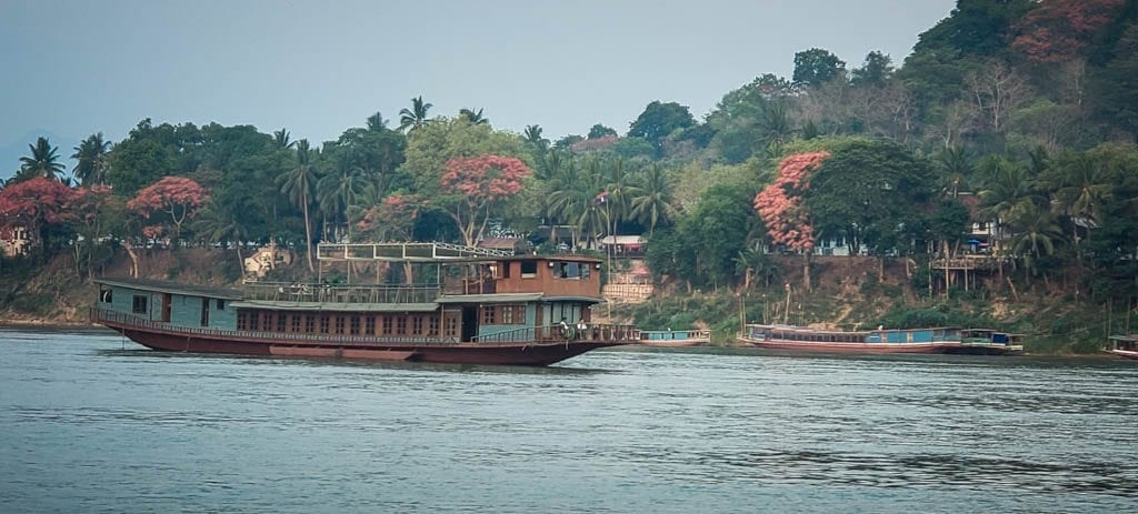 A boat on the Mekong River in Luang Prabang where you can release a fish and make a wish in Southeast Asia.