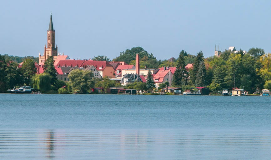 The sparkling lake and quaint church steeple visible from the Ravensbrück Concentration Camp