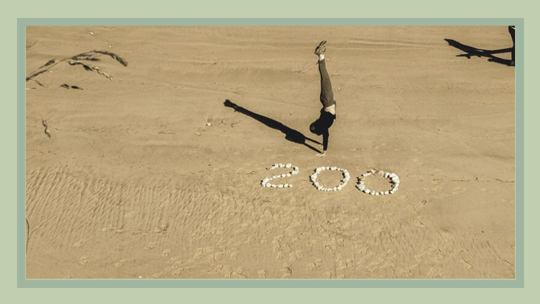 a woman does a handstand near the 200 mile marker on the camino del norte