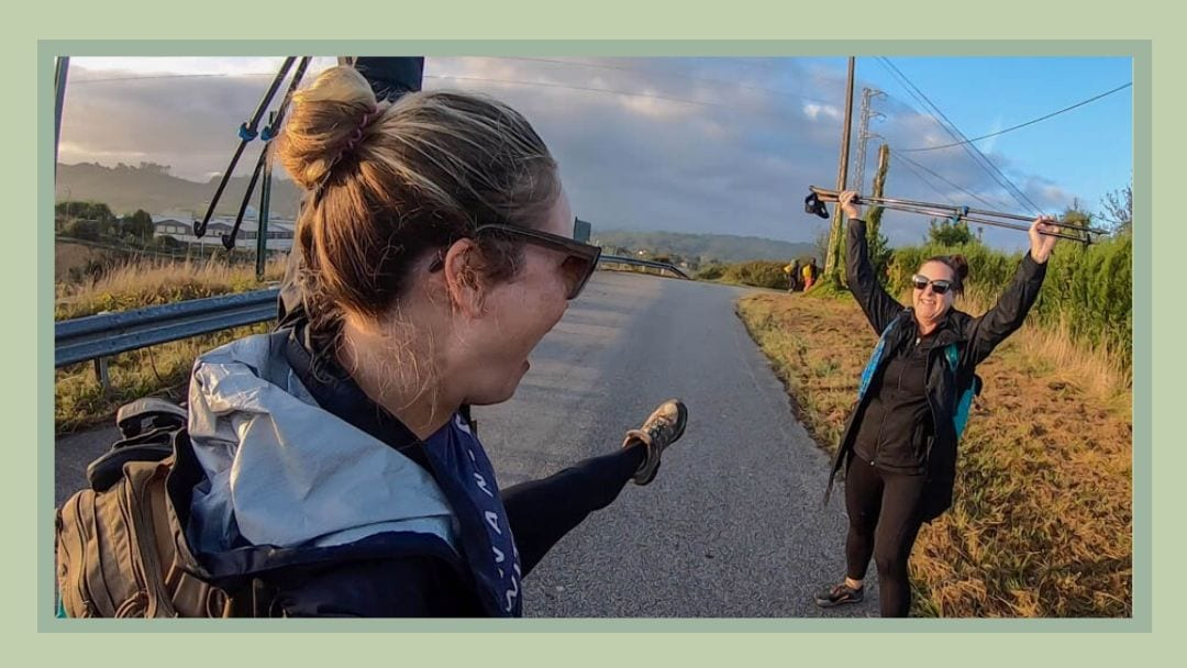Two women hold walking sticks over head on the Camino del Norte