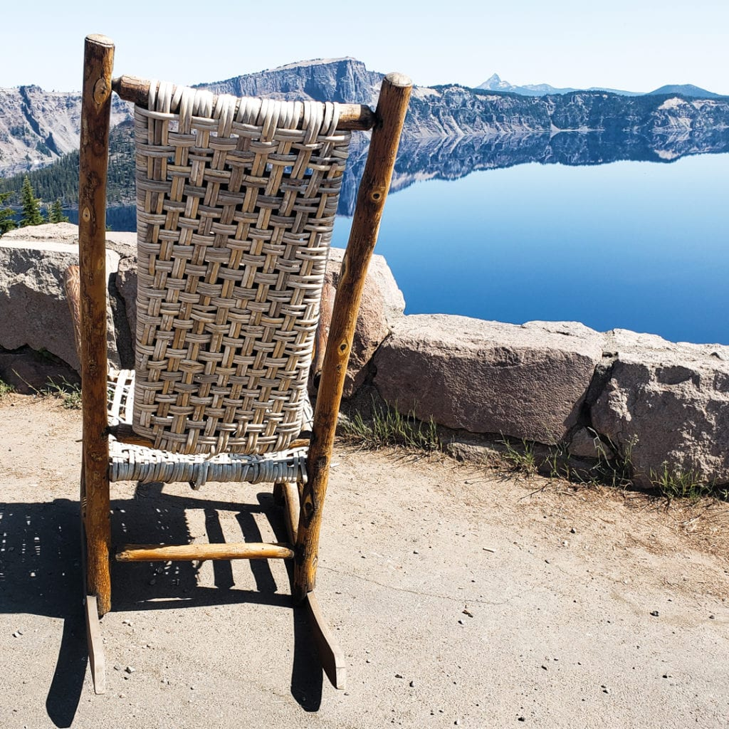 Empty chair with crater lake in distance