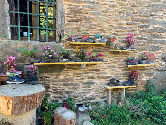 boots on a wall near santiago on the camino de santiago